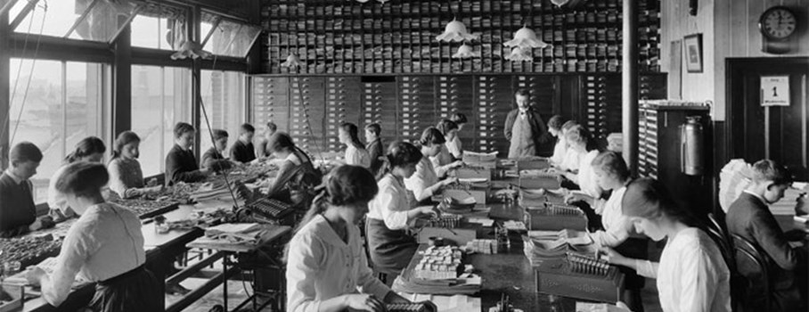 The Comptometer room at the Stratford Co-operative Society, showing girls and boys working on model 'E' comptometers. The comptometer, invented in 1887 by American, Dor Felt, was the first successful manual calculating machine. Many of the boys and girls look very young to be at work. The school leaving age was only raised to 14 in the Education Act of 1918 so they could well have been younger than that.