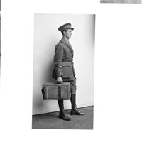 A soldier carrying a wooden case