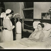 A nurse administering oxygen therapy to a patient in a hospital bed