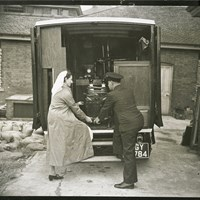 A radiographer and assistant lifting mobile radiography and X-ray equipment from a van