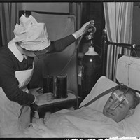A nurse giving oxygen to a patient, Guy's Hospital, Great Maze Pond, Southwark, Greater London