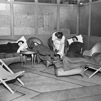 A view of women suffering from shock under blankets on sofas and armchairs, attended to by a nurse