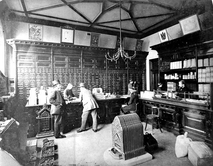 Customers buy seed at the Sutton's Seeds shop.  The drawers behind the counter presumably hold seeds, while the cashier sits behind the counter to the right.   A solid fuel heater stands in the centre of the floor.