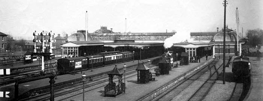 Several steam trains standing at the station platforms, with the Victorian station buildings in the background.Slough Station booking hall, booking office and travel centre were built in 1882. The Great Western Railway from London to Bristol was built in the 1830s and the first Slough Station opened in 1840. The present station is the fifth one and was built when the number of lines was increased.