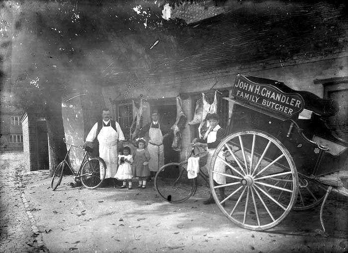 A view of the yard outside the butchers shop with hanging carrasses behind the group of people posing for the camera. In the foreground is cart used to transport goods and a young delivery boy with his bicycle.