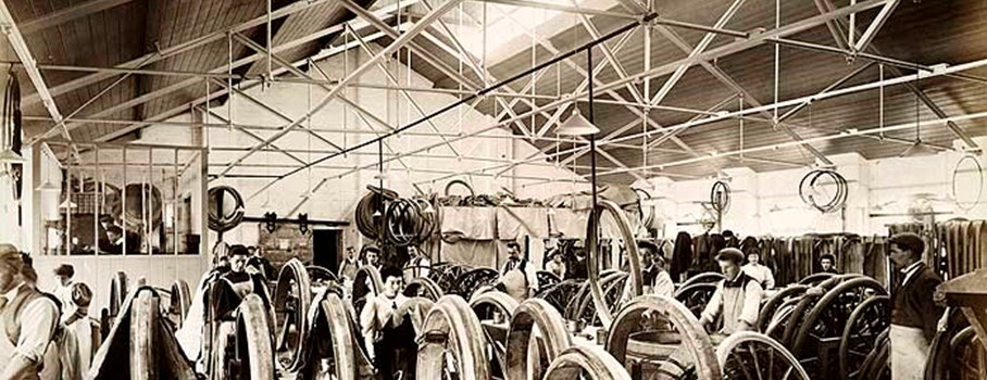 The interior of the carriage tyre shop showing employees at work. All the workers are dressed in their everyday clothes and wearing aprons to protect them. These jobs were skilled, indoor jobs rather than manual labour and this is reflected in the clothing.