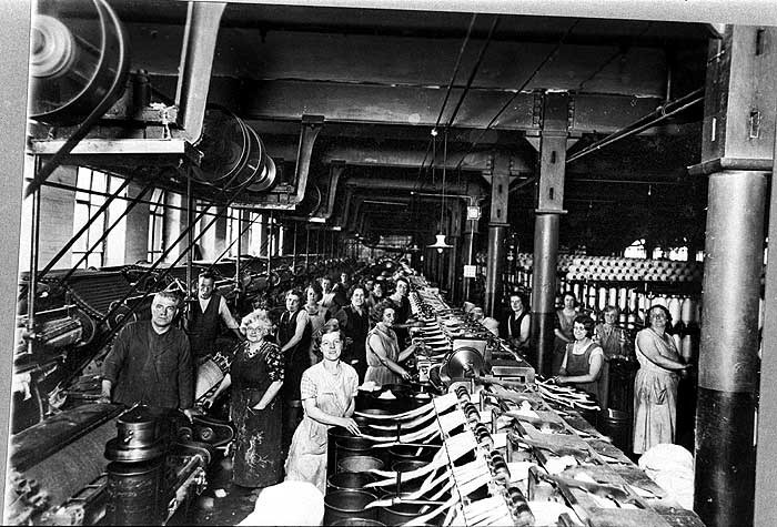 The machines to the right of this picture are carding machines. These used spiked drums in which the cotton was rotated. This process aligned the fibres, which were then placed in buckets as lengths or 'slivers'. The slivers were combined on a doubling frame, which is the machine that most of these women are working on.