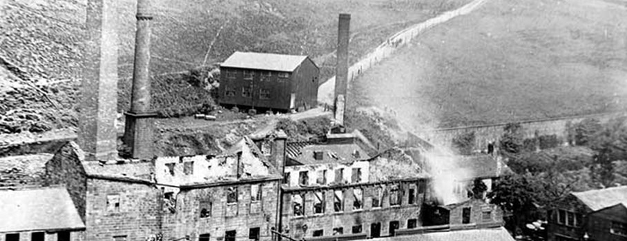 This mill was originally known as Jumble Hole Mill. It was first mentioned in 1788. Between 1815 and 1826 it was owned by Christopher Rawden who owned several mills in the locality. On 11th August 1899 the mill was destroyed by fire. This photograph could have been taken after the fire. The mill was altered and extended during the 19th and 20th century. The 1947 Yorkshire textile Industry directory has an entry for Jumble Hole Mill: 'Cocker and Co (1929) Ltd. (bleaching, dyeing and finishing of blacks and colours; rayons; crepes; cashmeres; brocades; muslins) Cockers closed in the 1950s, but the mill was later used for silk dyeing.
