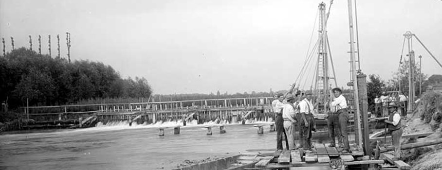 Workmen operating a pully mechanism to lift large wooden poles during construction of the new weir, with the older one in the background.