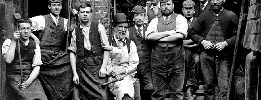 These are the foundrymen of James Hews the Ironmongers. They are standing in the yard of their work premises with various iron pipes in the background and some of the tools of their trade. The men are wearing different clothes and hats that give clues to their jobs and status. The boss, office workers or possibly shop assistants are wearing a jacket, collar and tie. The workers and apprentices have flat caps and leather aprons. The men wearing bowler hats would have been overmen (foremen).