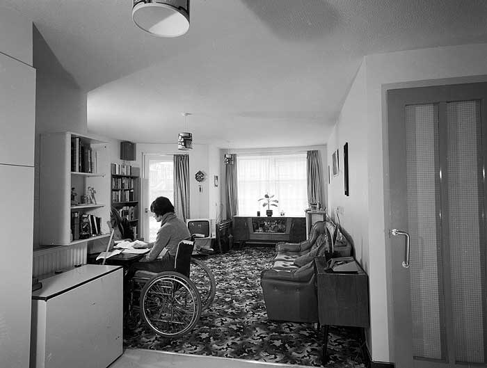 A young woman seated in a wheelchair at a desk in the living room of a sheltered accommodation flat at Whitby Court on the Holloway Estate in Islington. Whitby Court a purpose built development of low rise accessibly designed flats and houses for disabled people.