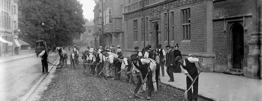 Workmen using pickaxes and shovels to prepare a road surface outside the Examination Schools, designed by T.G. Jackson, built in 1882.