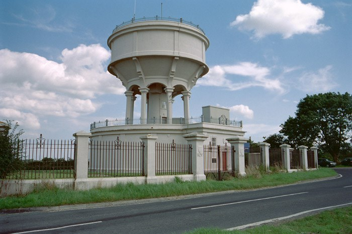 This water tower at Battys corner is dated 1916. It was built from reinforced concrete for Hull Corporation Waterworks. A plaque is inscribed: CITY OF HULL WATERWORKS WITHENSEA AND SOUTH HOLDERNESS SUPPLY 1916. The base contains pumps and a 300,000 gallon tank. The upper tank, of 100,000 gallon capacity, surrounds the central tower which carries a spiral staircase and pipe-work dated 1914.  Read official list description.