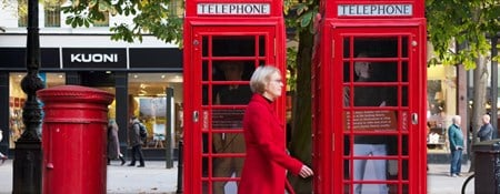 Woman walking past telephone kiosks in Cheltenham