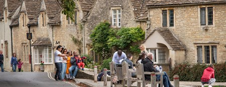 People sitting on benches with stone cottages in the background