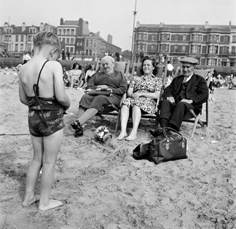 People sitting on the beach in post-war Blackpool