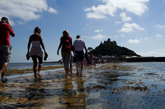 Rear view of people walking towards St Michael's Mount, Cornwall