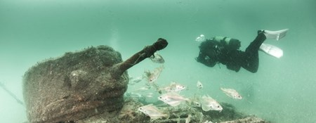 The submerged remains of a tank being recorded by a diver.