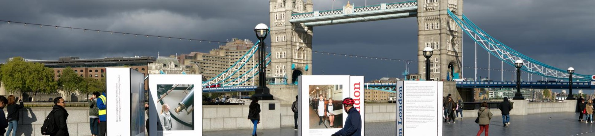 Tower Bridge, London with pedestrians and cyclists in the foreground stopping to look at Historic England's I am London exhibition panels in a pedestrianised area on the south bank.