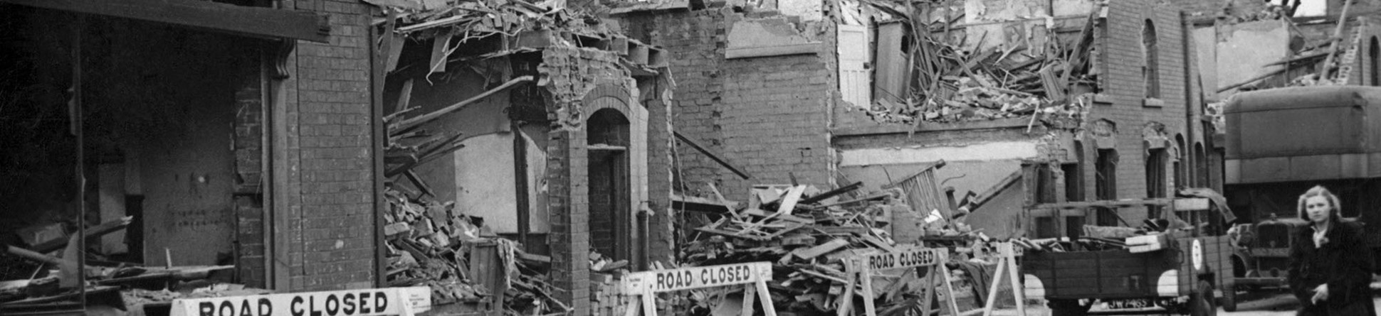 In front of the damaged houses are 'road closed' signs and a woman walking along in the road.
