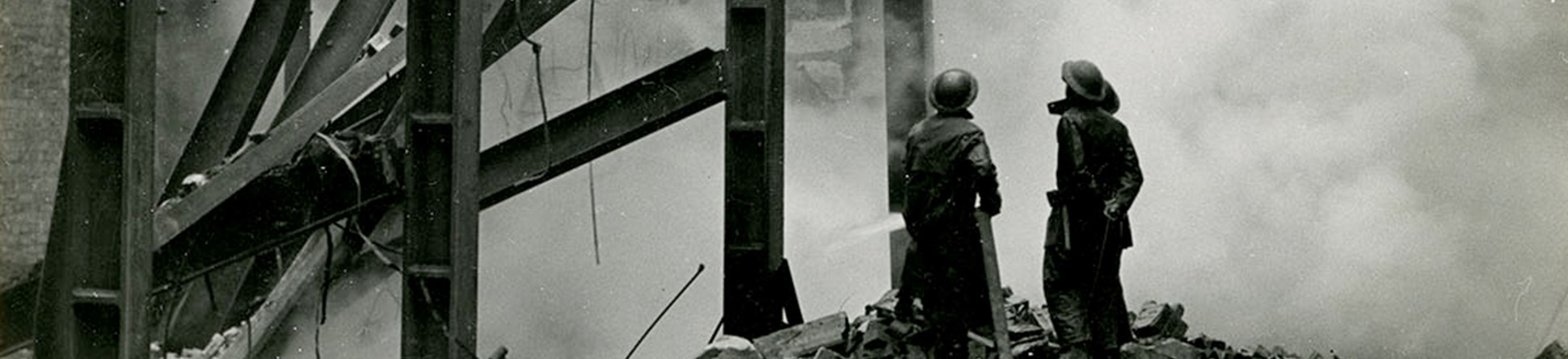 Two fire fighters stand on a pile of rubble next to steel girders looking up at a bomb damaged building partially shrouded by smoke.