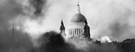 The dome of St Paul's emerging out of a cloud of smoke that engulfs burning buildings in the foreground.