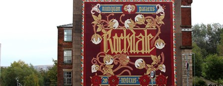 A mural featuring the name of the town, its Latin motto, cotton bolls and red roses, created on the side of a mill building.