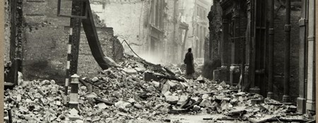 A person in a long coat and hat stands in rubble after the Brewers Hall was destroyed.