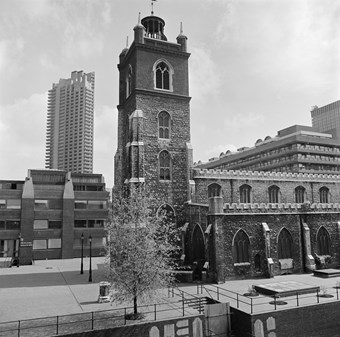 A black and white photo showing St Giles church from the South side, with a tower block in the background.