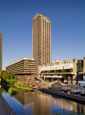 Colour photo showing the Barbican Centre next to a narrow lake, with a high tower in the background.