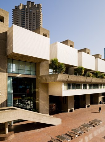 A colour photo showing a side view of part of the Barbican complex. A rectangular sand coloured apartment building with small palm trees on balconies can be seen in the foreground, with a tower block in the background.