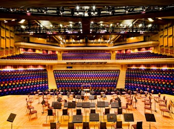 A colour photo showing the interior of a concert hall in the Barbican centre. Rainbow coloured rows of seats extend in the background, overlooking the stage in the foreground with seats for musicians.