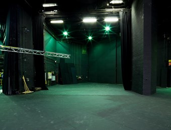 A digital colour photograph showing the backstage area of the Pit theatre at the Barbican centre. Green lights shine on the dark grey walls, with various equipment stored in the background.