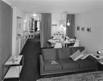 A black and white photo showing the interior of a flat with a large sofa and sitting room in the foreground, and a kitchen area in the background.