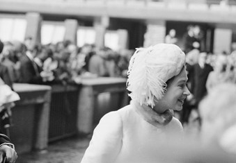 A black and white photo showing Queen Elizabeth II dressed in white at the Barbican Arts Centre, with a blurred view of a crowd of people in the background.