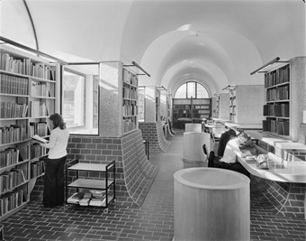 A black and white photo showing the interior of the Guildhall School of Music and Drama Library. The library's floors and walls are partially covered with bricks, and three people are reading books in the area.