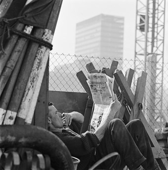 A black and white photo of a man sitting down with a newspaper, smoking a cigarette. The man is surrounded by the Barbican building site in progress, with a crane and tower in the background.