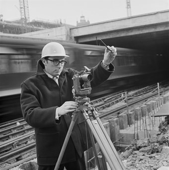 A black and white photo showing a surveyor wearing a hard-cap, taking measurements with a theodolite instrument, in front of a railway line with a speeding train passing.
