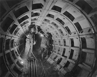 A black and white photo showing two workmen in a large tunnel at the Barbican site. The men are working on reinforcements with a few lights installed in the tunnel.