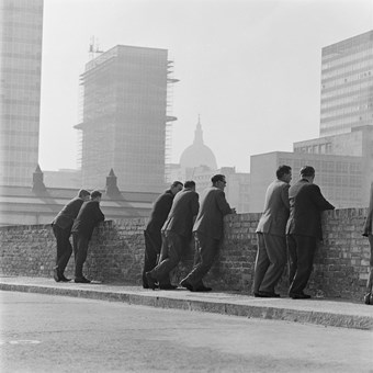 A black and white photo showing a group of men in suits leaning against a brick wall. The background shows the dome of St Paul's Cathedral, as well as office blocks.