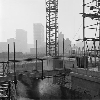 A black and white photo showing the Barbican Estate under construction. Cranes and scaffolding are in the foreground, while St Giles church and the dome of St Paul's Cathedral are visible in the background.