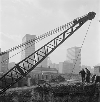 A black and white photo showing a building site with a crane in the background, holding a bucket swinging in the middle of the photo. Tower blocks are visible in the background and a few people are on site.