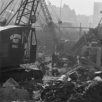 A black and white photo showing the building site of the Barbican estate, with a crane in the foreground that has a sign on it saying 'Holmpress Piles of Hull'. Men are working in the background amongst bricks and debris.
