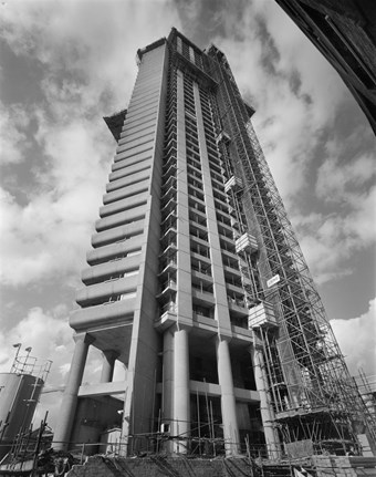 A black and white photo showing the Cromwell Tower under construction. The tower is seen from a low angle, with scaffolding surrounding it.