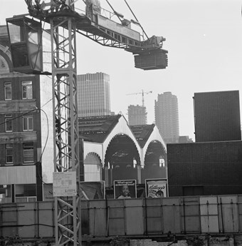 A black and white photo showing Liverpool Street station with a crane in the foreground. Tower blocks of the barbican can be seen under construction in the background.