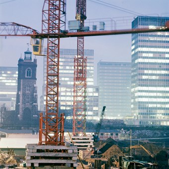 A colour photo showing the Barbican estate under construction, with a red crane in the foreground. St Giles Church and modern tower blocks can be seen in the background.