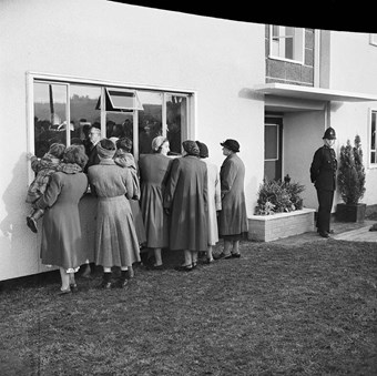 A group of women holding children peer through the window of a newly built Easiform home. A police stands guard at the doorway