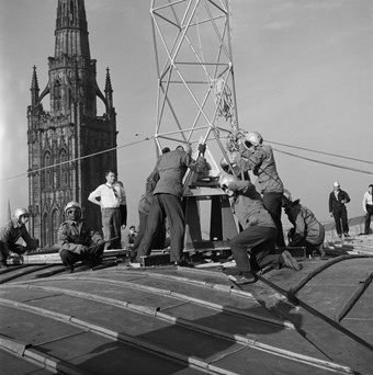Men in helmets working to manoeuvre a metal frame. Six other men stand observing. The spire of the old cathedral is in the background.