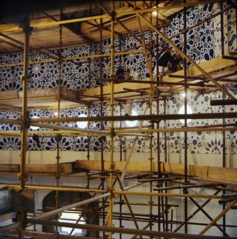 Two men on intricate scaffolding complete tiling at the London Central Mosque.