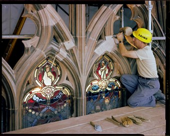 A stonemason in yellow Laing hardhat works on stone around stained glass at the Carlisle Cathedral.
